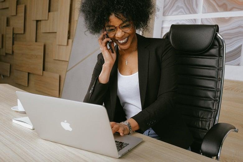 Dame jobber hjemmefra mens hun snakker med kolleger på telefonen