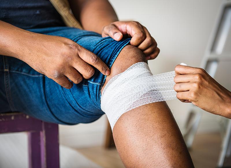 person-legge-bandasje-på-kne-og-utøver-førstehjelp