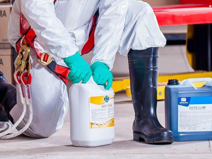 mann-i-vernedrakt-og-vernehansker-håndterer-kjemikalier